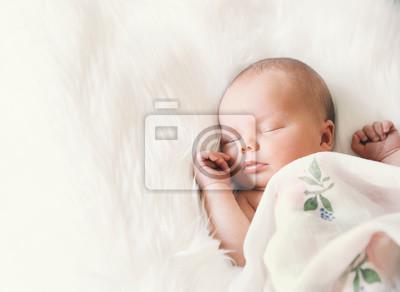 Fototapeta Sleeping newborn niemowlęcia w opakowaniu na białym koc.