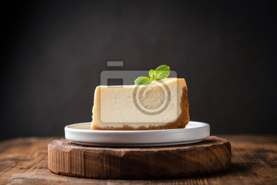 Fototapeta Slice of cheesecake with mint leaf on wooden cake stand over black background. Copy space for text
