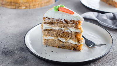 Fototapeta Slice of homemade carrot cake with cream cheese frosting on plate on gray stone table background