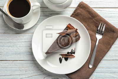 Fototapeta Slice of tasty chocolate cake and cup of coffee served on wooden table, top view