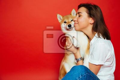 Fototapeta Śliczna brunetki kobieta trzyma i obejmuje Shiba Inu psa na płaskim czerwonym tle w białej koszula i cajgach. Miłość do zwierząt, koncepcja zwierząt domowych