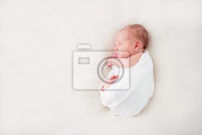Fototapeta Śliczne nowonarodzone dziecko leży w białym kocu. Skopiuj miejsce i widok z góry