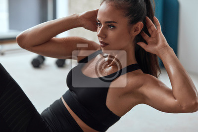 Fototapeta Slim fitness female in gym pumping press. Sweating strong fitnesswoman