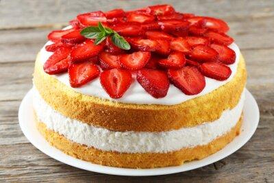 Fototapeta Słodkie ciasto z truskawkami na talerzu na szarym tle drewnianych