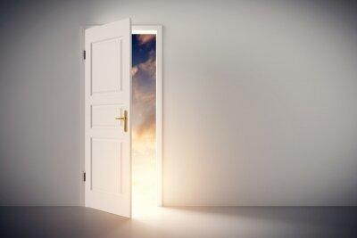 Fototapeta Słońce świecące przez pół otwartej klasyczne białe drzwi.