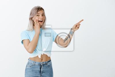 Słuchaj, to niesamowite. Portret pozytywnie wyglądającej modnej dziewczyny z tatuażem na ramieniu, uśmiechając się szeroko, wskazując w prawym górnym rogu i szepcząc sekret o interesującym miejscu nad