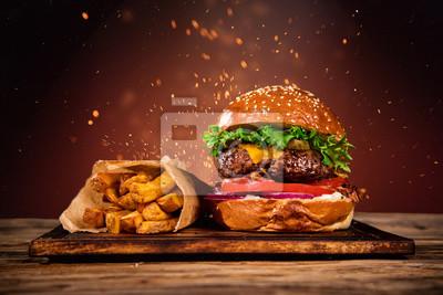 Fototapeta Smaczny hamburger z frytkami i ogniem.