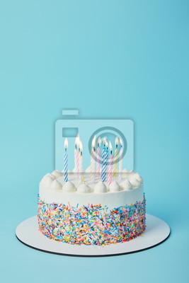 Fototapeta Smaczny tort urodzinowy z zapaleniem świec na niebieskim tle