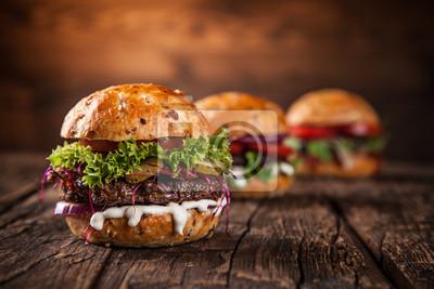 Fototapeta Smakowici hamburgery na drewnianym stole.