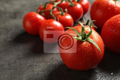 Fototapeta Smakowici soczyści pomidory na szarym tle, zbliżenie