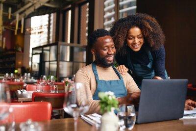 Fototapeta Small business owners using laptop in restaurant