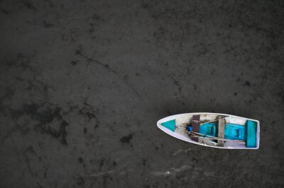 Fototapeta Small fishing boat floating on the water. View from top
