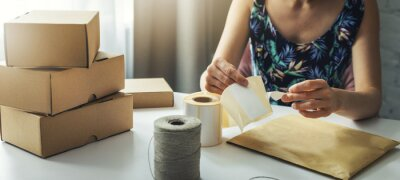 Fototapeta small online business owner preparing parcel shipping label at home for shipment delivery. banner