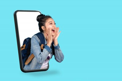 Fototapeta Smartphone pop up for advertising.Asian woman travel backpacker shouting open mouth through from screen mobile.Girl looking to aside copy space for present promotions.Digital marketing online cencept.