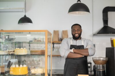 Fototapeta Smiling and friendly African-American small business owner, cafe manager, multiracial bakery waiter stands behind the counter in confident pose with arms crossed and looks at the camera
