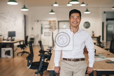Fototapeta Smiling Asian businessman leaning on a table in an office