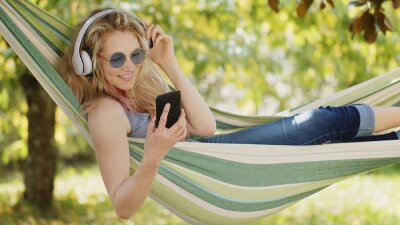 Fototapeta Smiling blonde woman wearing sunglasses using smartphone, listening to music with headphones, on hammock in the garden, leisure and summer concept for using internet or social media