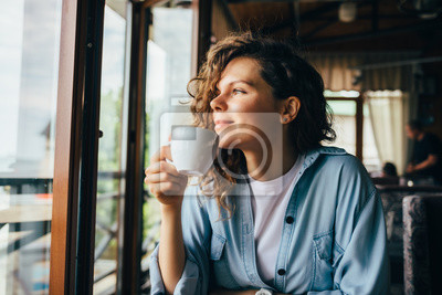 Fototapeta Smiling calm young woman drinking coffee