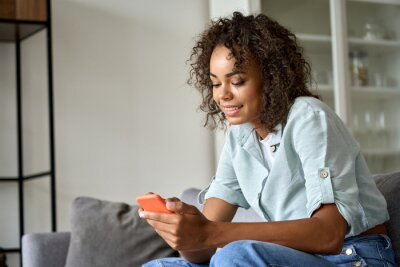 Fototapeta Smiling happy young African American woman holding cell phone sitting on sofa at home, using online mobile apps technology doing online shopping, dating in application, checking social media, texting.