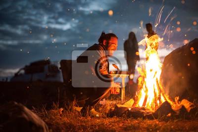 Fototapeta Smiling man next to a bonfire in the dark