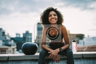 Fototapeta Smiling woman athlete taking a break during workout