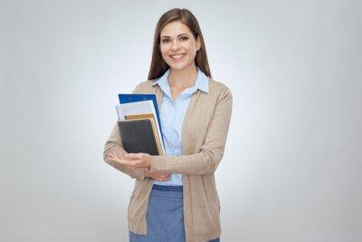 Fototapeta Smiling woman teacher holding books.