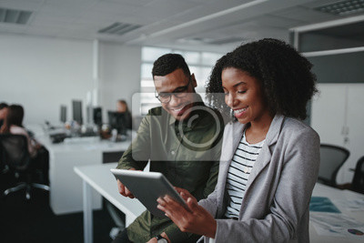 Fototapeta Smiling young african american professional businessman and businesswoman together working online with a digital tablet in office