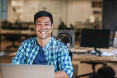Fototapeta Smiling young Asian designer using a laptop at his desk