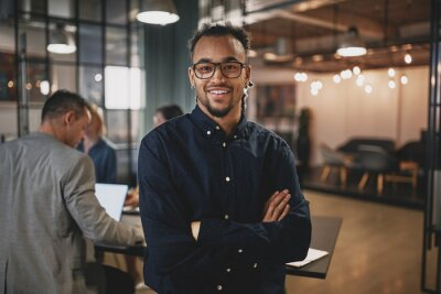 Fototapeta Smiling young businessman standing in a modern office