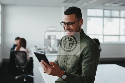 Fototapeta Smiling young businessman touching smartphone and checking online information in the modern office