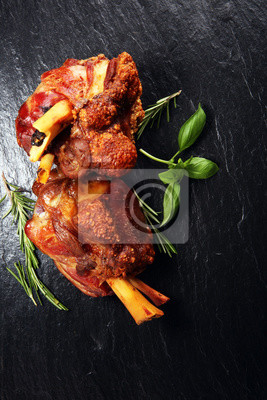 Smoked ham hock with herbs and spices on stone plate.