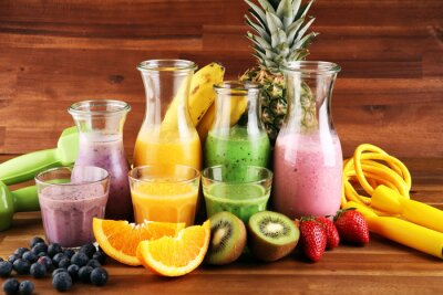 Smoothie variation. Healthy lifestyle concept. sport fitness equipment-several bottles with fruit and berry juices smoothies or milkshakes with jumping rope