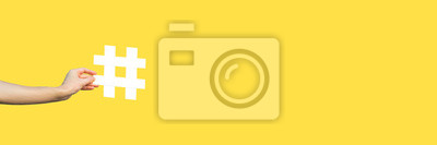 Fototapeta Social media concept. closeup of human hand holding and showing large big white hashtag sign. indoor studio shot, isolated on yellow background copyspace. marketing symbol, instagram followers.