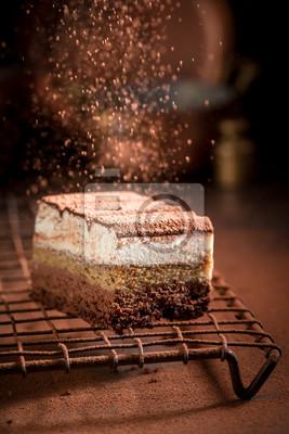 Fototapeta Spadający proszek kakaowy na ciasto tiramisu na metalowej siatce chłodzącej