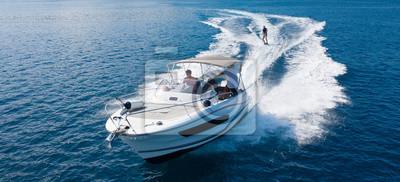 Fototapeta Speedboat with wakeboard rider on open sea