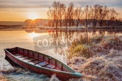 Fototapeta Spokojne wody jeziora, rzeki i łódź wiosłowa połowów na piękny wschód słońca w jesieni rano.