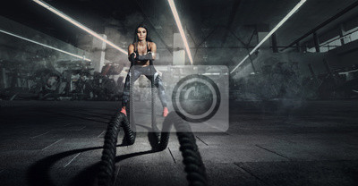Fototapeta Sport backgrounds. Powerful attractive muscular woman fitness trainer do battle workout with ropes at the gym.