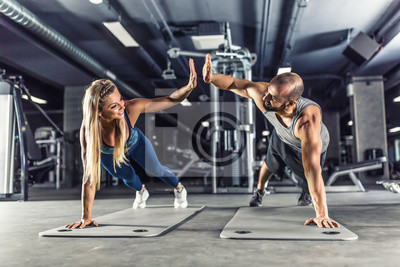 Fototapeta Sport couple doing plank exercise workout in fitness centrum. Man and woman practicing plank in the gym