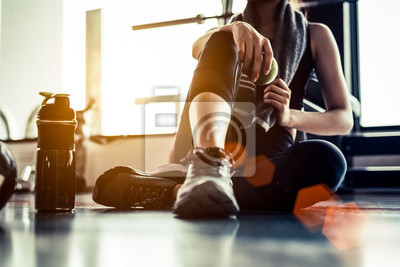 Fototapeta Sport kobieta siedzi i odpoczynku po treningu lub ćwiczeń w siłowni fitness z białka wstrząsnąć lub wody pitnej na podłodze. Relaks koncepcja. Trening siłowy i temat budowy ciała. Ciepły i fajny ton