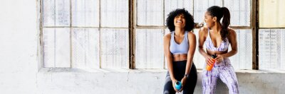 Fototapeta Sportive women talking in a gym while drinking water