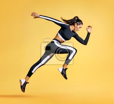 Fototapeta Sporty kobieta biegacz w sylwetce na żółtym tle. Fotografia atrakcyjna kobieta w modnym sportswear. Dynamiczny ruch. Widok z boku. Sport i zdrowy styl życia