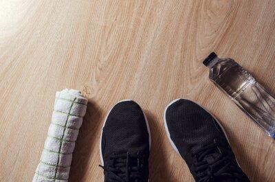 Fototapeta Sprzęt sportowy, trampki, woda, ręcznik na tle drewniane, mieszkanie lay