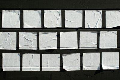Fototapeta Square sheets of paper glued on a black wooden board.