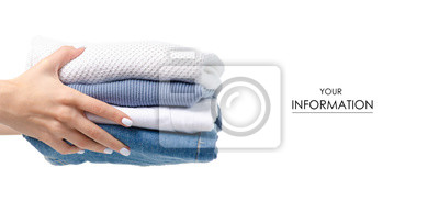 Fototapeta Stack of clothing jeans sweaters in hand pattern on a white background isolation