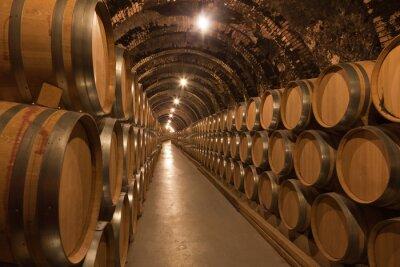 Fototapeta Stara winiarnia z beczkami pełnymi czerwonego wina którą otacza hiszpańska wioska jako fototapeta do winiarni