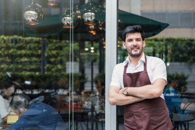 Fototapeta Startup successful small business owner man walking in his coffee shop or restaurant. Portrait of young caucasian man successful barista cafe owner