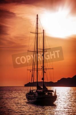 Fototapeta Stary statek płynie do zachodu słońca. Dramatyczny widok na morze
