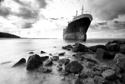 Fototapeta Statek towarowy osiadł na mieliźnie na skalistym brzegu brzegu, czarno-biały