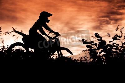 Fototapeta Status silhouate motocross skoki nad bursztynowym świetle tle zachodu słońca.