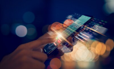 Fototapeta Stock exchange market concept, hand trader touching on smartphone with graphs analysis candle line on bokeh colors light in night atmospheric city.
